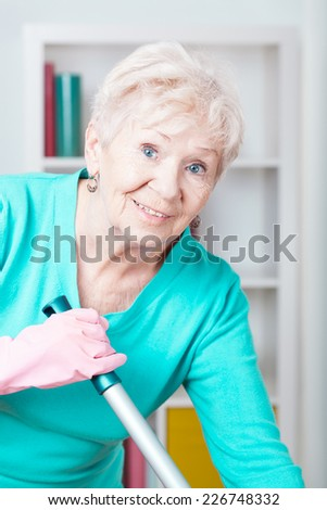 Portrait of smiling elderly woman washing floor - stock photo