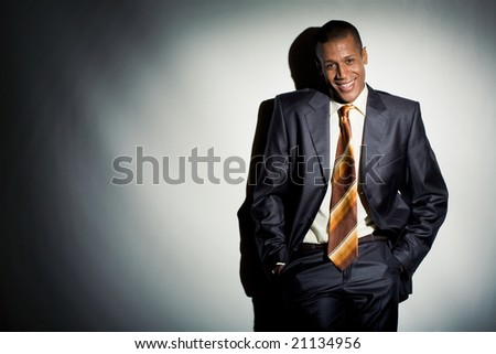 Portrait of smiling employer standing by lit wall and looking at camera - stock photo