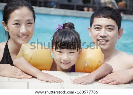 Portrait of smiling family in pool by the edge looking at camera - stock photo