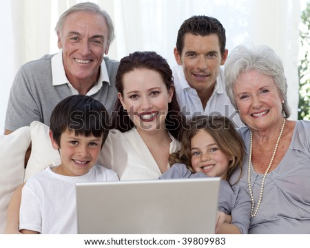 Portrait of smiling family sitting on sofa using a laptop - stock photo