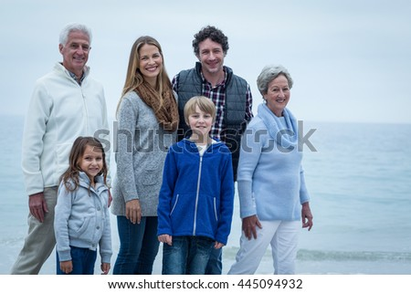 Portrait of smiling family standing at beach against sky - stock photo