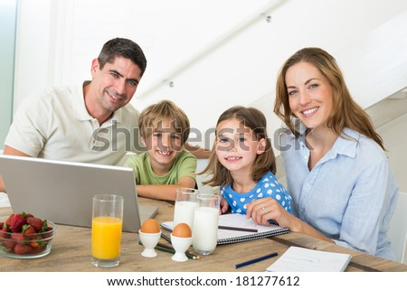 Portrait of smiling family using laptop while having breakfast at home - stock photo