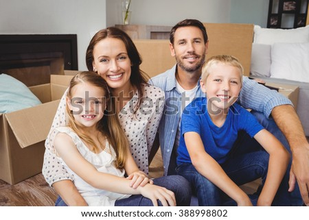 Portrait of smiling family with cardboard boxes at home - stock photo