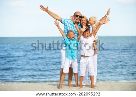 Portrait of smiling family with children having fun on the sunny beach with raised hands.