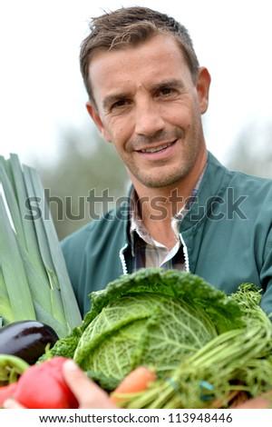 Portrait of smiling farmer holding vegetables basket - stock photo
