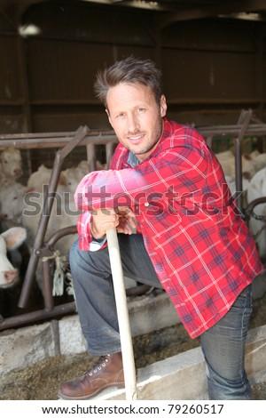 Portrait of smiling farmer in barn - stock photo
