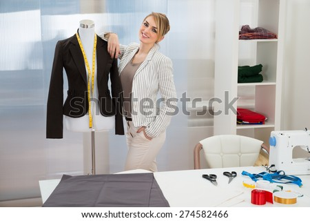Portrait Of Smiling Fashion Designer With Dressmakers Model - stock photo