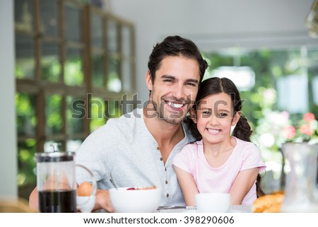 Portrait of smiling father and daughter at table in home - stock photo