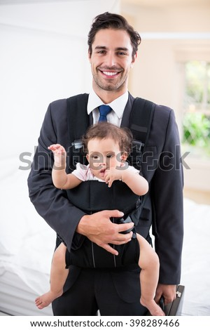 Portrait of smiling father carrying baby while standing at home - stock photo