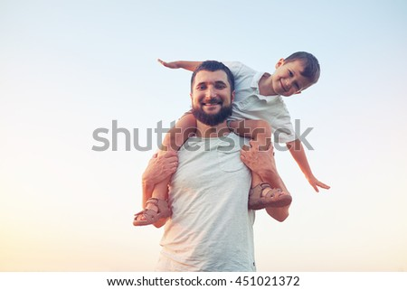 Portrait of smiling father holding his small son on shoulders against sunset sky