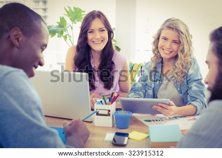 Portrait of smiling female business people using digital tablet at desk in office