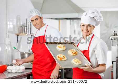 Portrait of smiling female chef holding small pizzas on tray with colleague in background at commercial kitchen