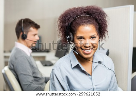 Portrait of smiling female customer service representative with male colleague in background at office - stock photo