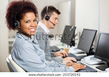 Portrait of smiling female customer service representative with male colleague working in office - stock photo
