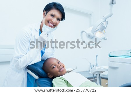 Portrait of smiling female dentist examining boys teeth in the dentists chair - stock photo
