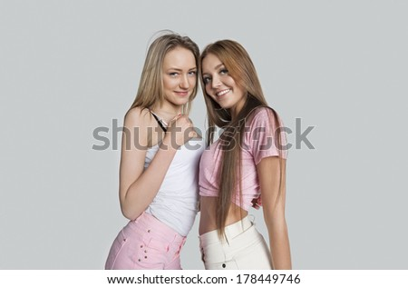 Portrait of smiling female friends against white background - stock photo