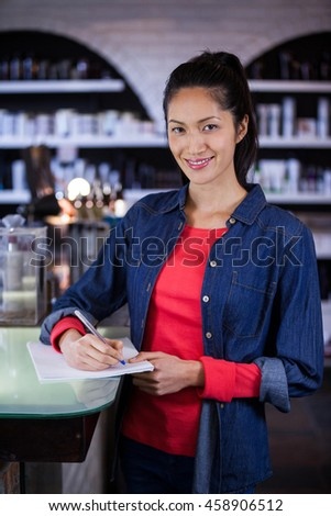 Portrait of smiling female hairdresser filling a form at a salon