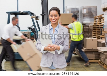 Portrait of smiling female manager holding files during busy period in warehouse - stock photo