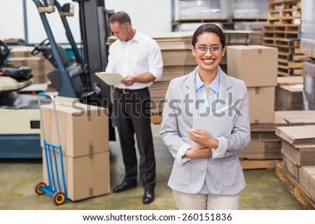 Portrait of smiling female manager holding files during busy period in warehouse