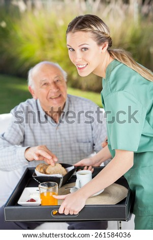 Portrait of smiling female nurse serving breakfast to senior man in nursing home - stock photo