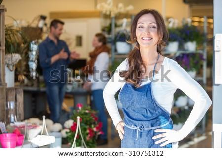 Portrait of smiling female owner with customers in background at flower shop - stock photo