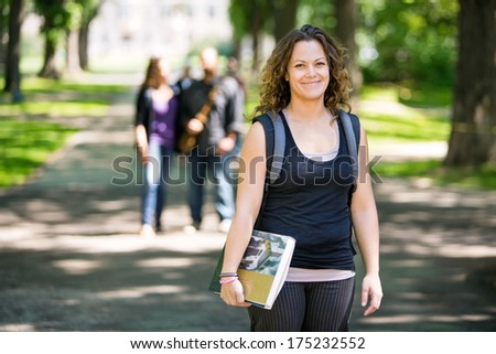 Portrait of smiling female student with backpack and book standing on campus road