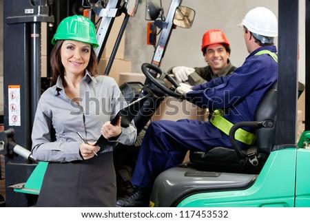 Portrait of smiling female supervisor with foremen communicating at warehouse - stock photo