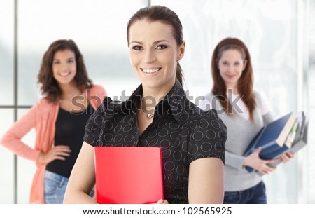 Portrait of smiling female teacher with happy students in background.