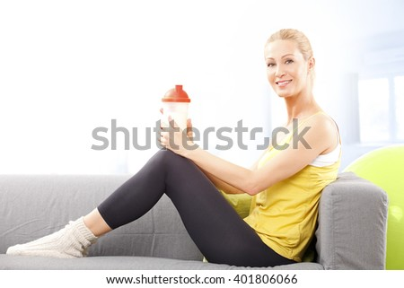 Portrait of smiling fit woman holding in her hand a shaker while sitting on couch after home workout. - stock photo