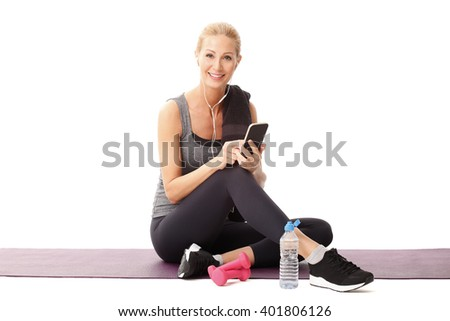 Portrait of smiling fit woman sitting on yoga mat and using her mobile phone after fitness workout. Isolated on white background.