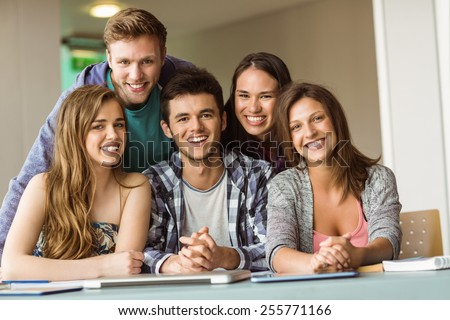 Portrait of smiling friends posing near their laptop at school - stock photo