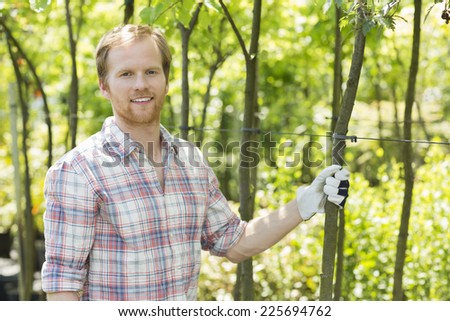 Portrait of smiling gardener standing at plant nursery - stock photo
