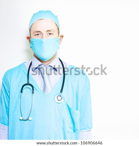 Portrait of smiling general practitioner doctor wearing blue surgery mask against white copyspace hospital wall - stock photo