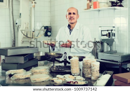 Portrait of smiling germany mature male with packing of turron in food factory