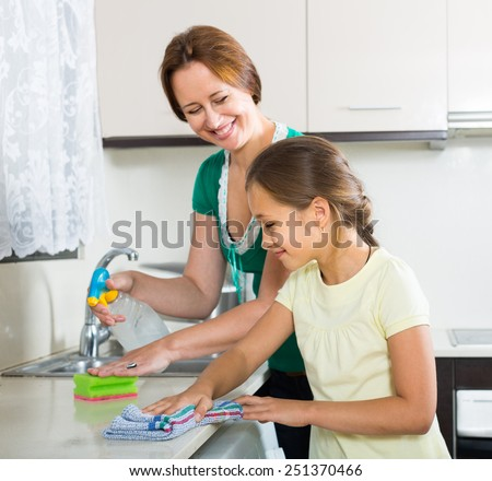 Portrait of smiling girl and american mom tidy kitchen up - stock photo
