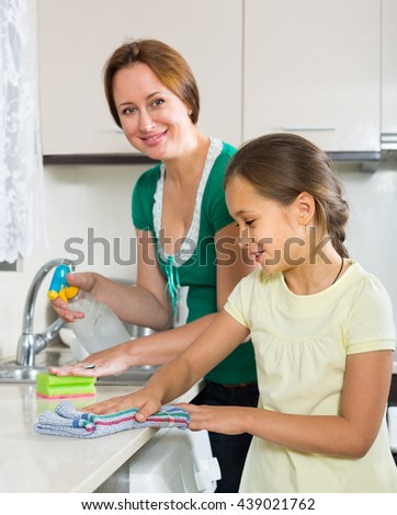 Portrait of smiling girl and happy mom tidy kitchen up - stock photo