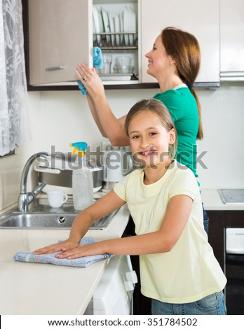 Portrait of smiling girl and mom washing kitchen up - stock photo