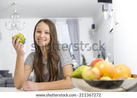Portrait of smiling girl holding apple while sitting at table in house
