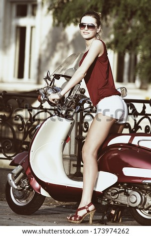 Portrait of smiling girl on scooter holding a helmet - Outdoor on street .Retro shot. Fashion art photo  - stock photo