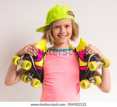 Portrait of smiling girl wearing peaked cap and holding roller skates on her shoulders against white background. - stock photo