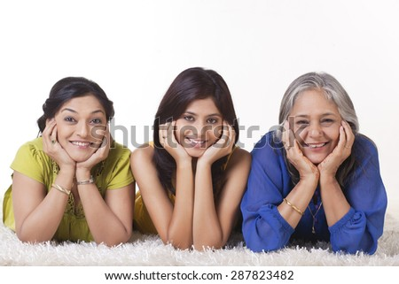 Portrait of smiling girl with her mother and grandmother lying on carpet - stock photo