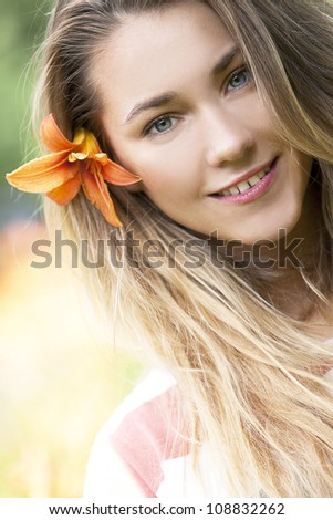 Portrait of smiling girl with lily flower in hair - stock photo