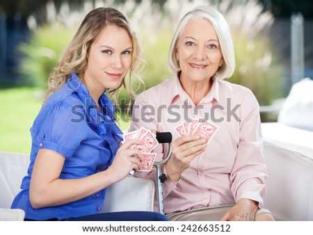 Portrait of smiling granddaughter and grandmother playing cards at nursing home porch - stock photo