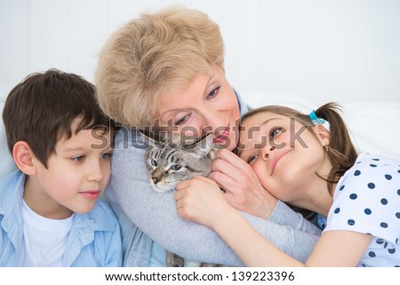Portrait of smiling grandmother and grandchildren hugging on sofa with granny's cat - stock photo