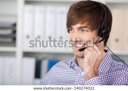Portrait of smiling handsome customer service executive using headset in office - stock photo
