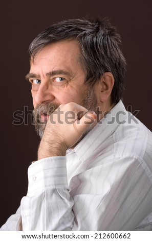 Portrait of  smiling handsome senior man looking at the camera on a brown background