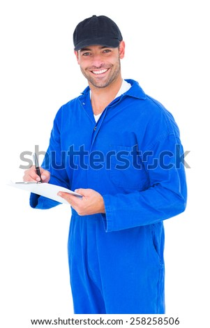 Portrait of smiling handyman in blue overall writing on clipboard over white background - stock photo