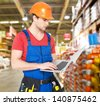 Portrait of smiling handyman with laptop working warehouse - stock photo