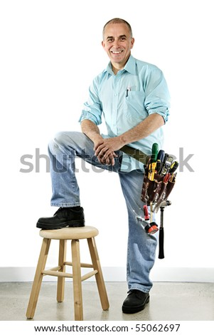 Portrait of smiling handyman with tool belt and stool - stock photo