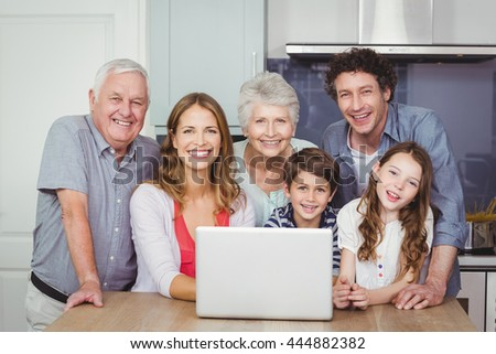 Portrait of smiling happy family with laptop in kitchen at home - stock photo